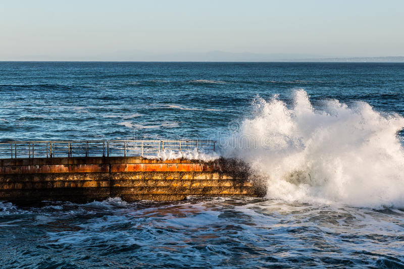 La piscine des enfants de La Jolla à la marée haute avec la vague se brisante images stock