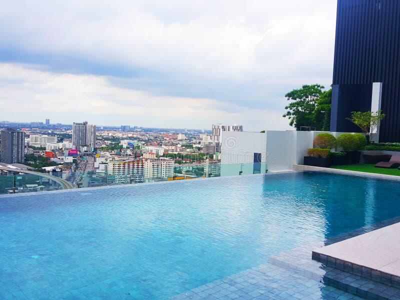 La piscine est dans un logement ayant beaucoup d'étages et donne sur la ville images libres de droits