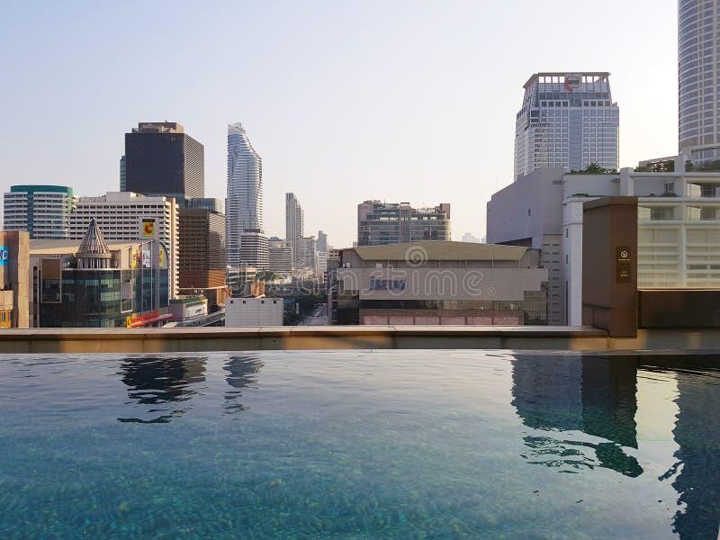 La piscine illimitée dans l'hôtel sur le toit avec vue sur les maisons au centre de la ville photo libre de droits