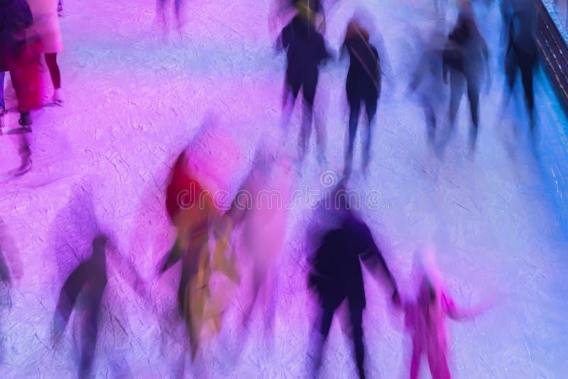 La pista de patinaje Blurred con la gente por la tarde mide el tiempo al aire libre en el parque el invierno Concepto del deporte foto de archivo