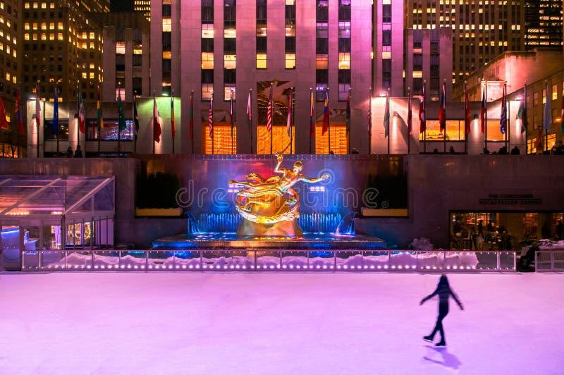 La pista del patín de hielo del centro de Nueva York Rockefeller con la iluminación colorida y la gente están patinando imagen de archivo