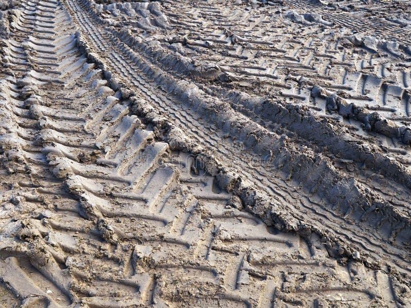 La pista del tractor cansa las ruedas en la tierra del fango imagenes de archivo