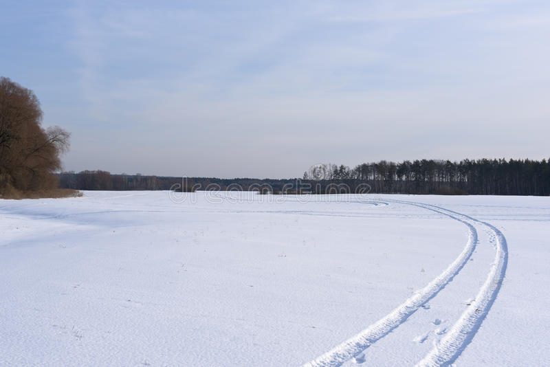 La pista en un campo nevado que se va lejos fotos de archivo