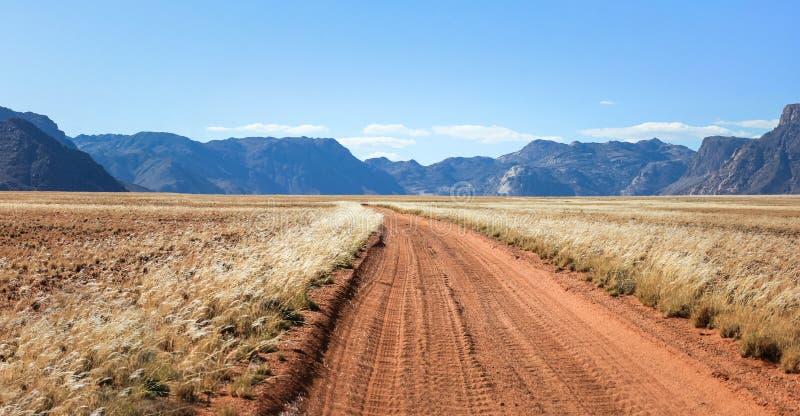 La pista recta del camino de tierra del desierto pasa el prado hacia las montañas imágenes de archivo libres de regalías
