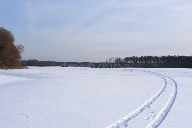 La pista su un campo innevato che va lontano fotografie stock