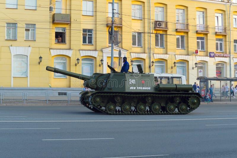 La pistola dell'artiglieria pesante ISU-152 sta guidando lungo il viale di Lenin contro lo sfondo della costruzione gialla fotografia stock