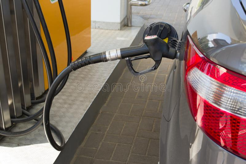 La pistola per combustibile è inserita nel carro armato di gas dell'automobile fotografia stock
