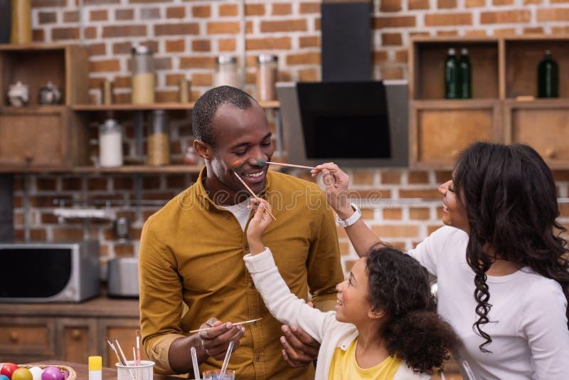 La pittura afroamericana della figlia e della madre genera il fronte con le pitture, concetto di pasqua immagini stock libere da diritti
