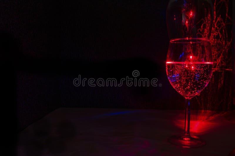 La pittura della luce laser del bicchiere del vino dell'acqua e bolla e la spruzzata dell'acqua dallo sguardo di vetro gradiscono fotografia stock libera da diritti