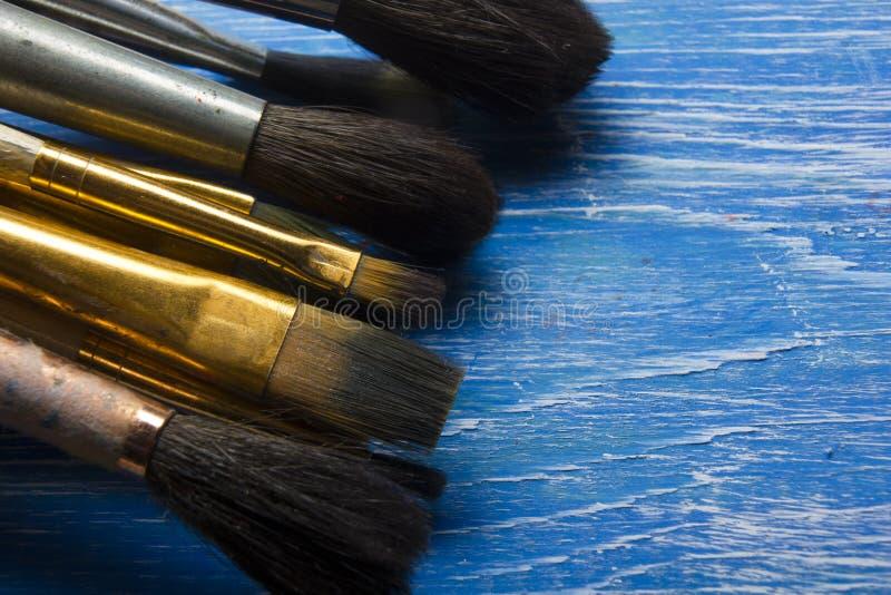La pittura foggia i pennelli della tavolozza di colore e dell'artista su fondo artistico astratto fotografia stock