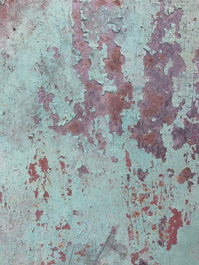La pittura incrinata su una superficie di metallo, arrugginisce fondo strutturale immagini stock