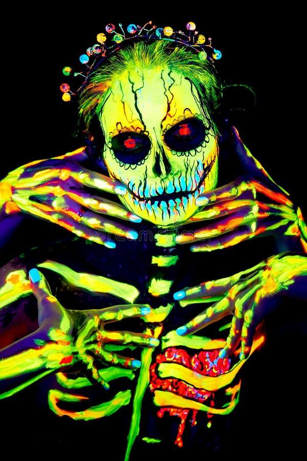 La pittura UV di body art di helloween lo scheletro femminile immagini stock libere da diritti
