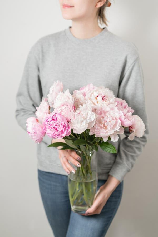 La pivoine mignonne et belle fleurit chez des mains du ` s des femmes Beaucoup de pétales posés Groupe pâle - fleurs roses de piv photo stock