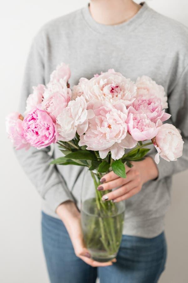 La pivoine mignonne et belle fleurit chez des mains du ` s des femmes Beaucoup de pétales posés Groupe pâle - fleurs roses de piv photographie stock libre de droits