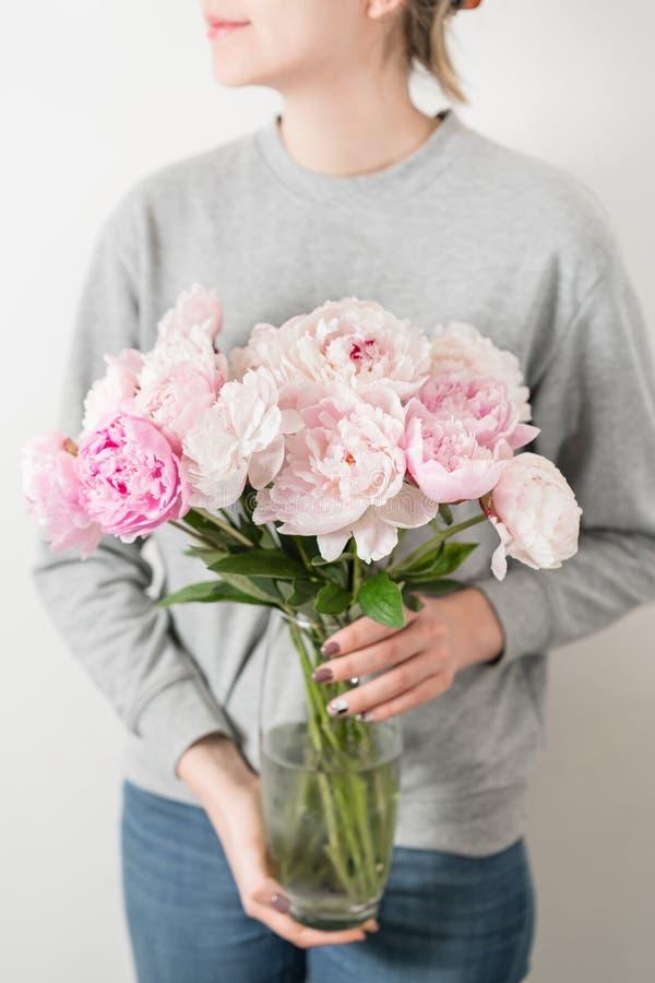 La pivoine mignonne et belle fleurit chez des mains du ` s des femmes Beaucoup de pétales posés Groupe pâle - fleurs roses de piv photo libre de droits