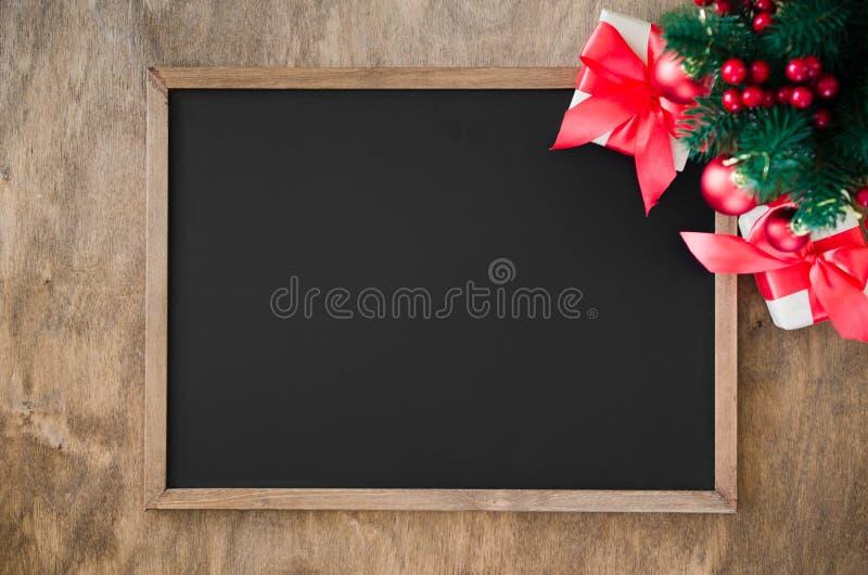 La pizarra vacía con la decoración de la Navidad, caja de regalo roja, abeto ramifica fotos de archivo