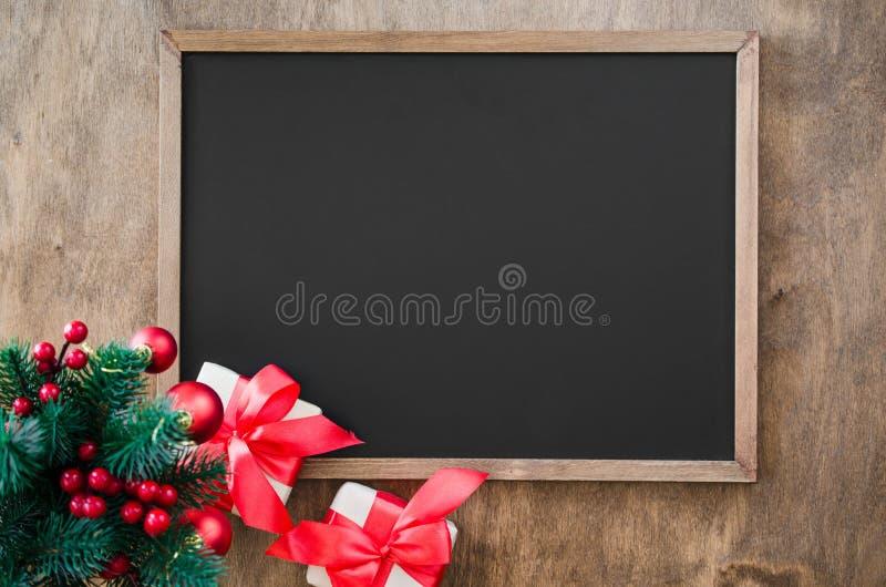 La pizarra vacía con la decoración de la Navidad, caja de regalo roja, abeto ramifica imagen de archivo