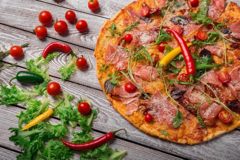 La pizza è servito alla pizzeria con i peperoni e le insalate Pizza con le verdure su un fondo leggero Spuntini classici del part fotografia stock libera da diritti