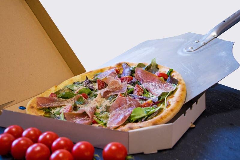La pizza caliente cocinada en una pala se empuja en una caja de embalaje, entrega de la comida foto de archivo