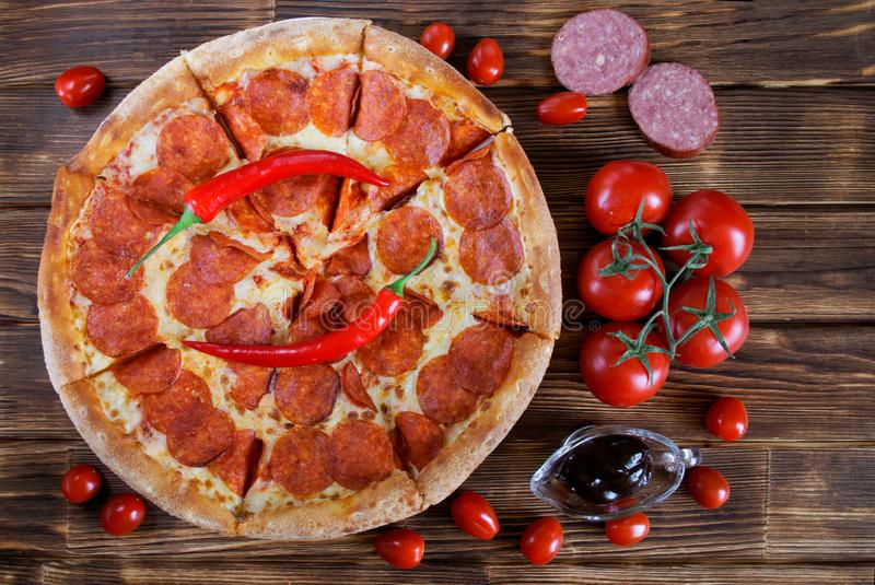 La pizza casalinga con salame e le merguez rosse dei peperoncini rossi sta trovandosi su una superficie di legno delle plance del fotografia stock libera da diritti