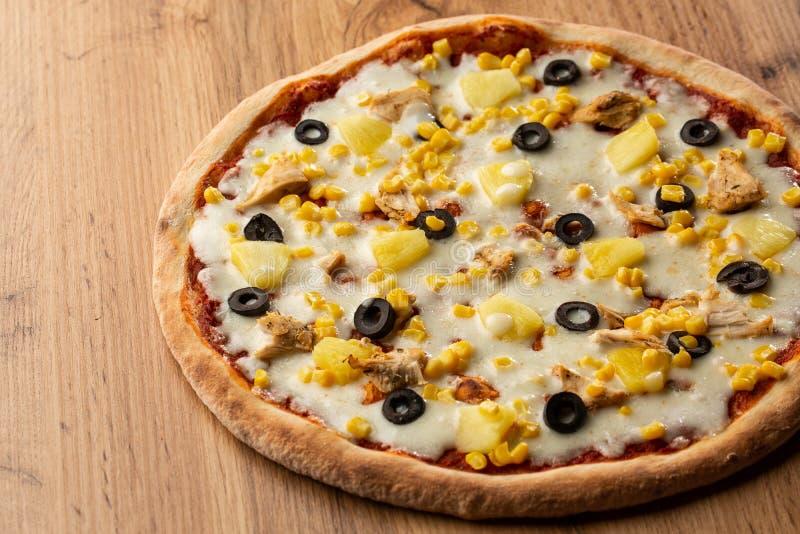 La pizza a complété avec le service de sauce, de poulet, de fromage et d'ananas du plat en bois sur la table en bois Photo de piz photographie stock libre de droits