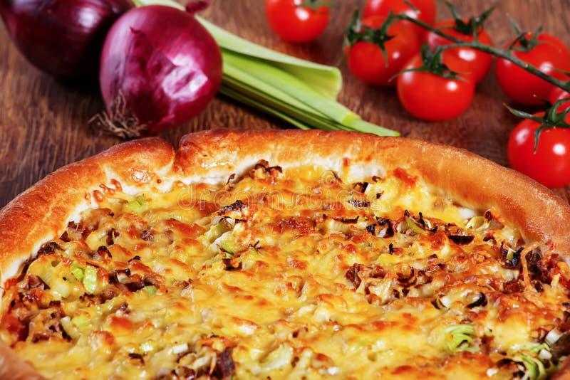 La pizza con il riempimento, il porro ed il formaggio del manzo è servito sulla tavola di legno fotografie stock