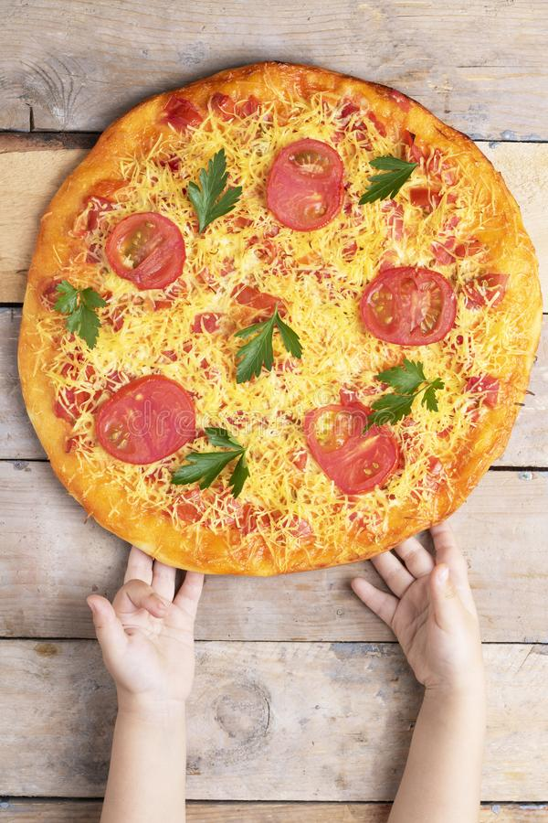 La pizza de Margarita con el queso y los tomates en la tabla de madera, manos de los niños lleva a cabo la pizza, la visión super imágenes de archivo libres de regalías