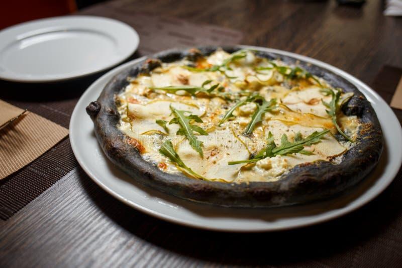 La pizza de queso negra sirvió en la tabla en restaurante fotos de archivo libres de regalías