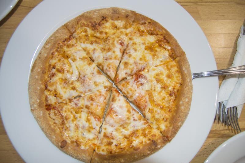 La pizza de queso recientemente cocida, corte apetitoso en pedazos miente en una placa blanca, una vista superior de la tabla y c foto de archivo