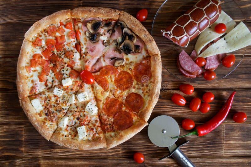 la pizza del Quattro-pezzo con le merguez, il salame, i peperoncini rossi, il prosciutto, i funghi, il formaggio ed i pomodori si fotografie stock