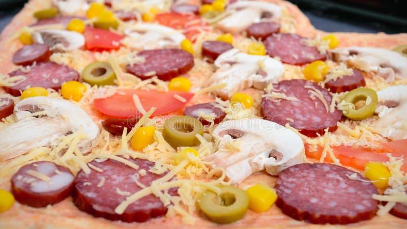 La pizza deliziosa in una forma del cuore, aspetta per cuocere Pizza con i funghi, salame, merguez, olive immagine stock