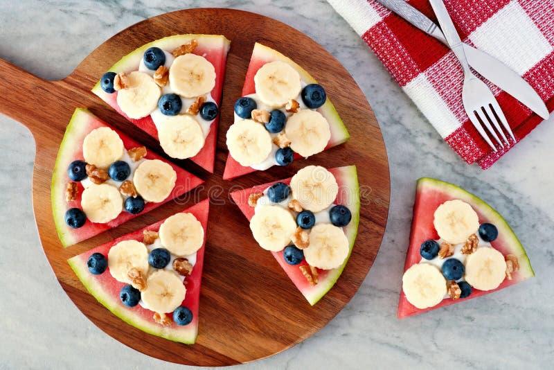 La pizza dell'anguria con le banane, i mirtilli ed il yogurt sul servizio imbarcano fotografia stock libera da diritti