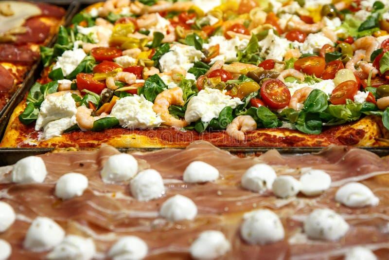 La pizza emportent des morceaux sur une stalle, une focacce italienne traditionnelle avec des tomates, des olives noires et un fr photo libre de droits