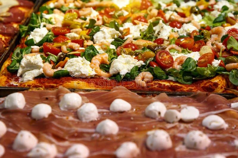 La pizza emportent des morceaux sur une stalle, une focacce italienne traditionnelle avec des tomates, des olives noires et un fr images libres de droits