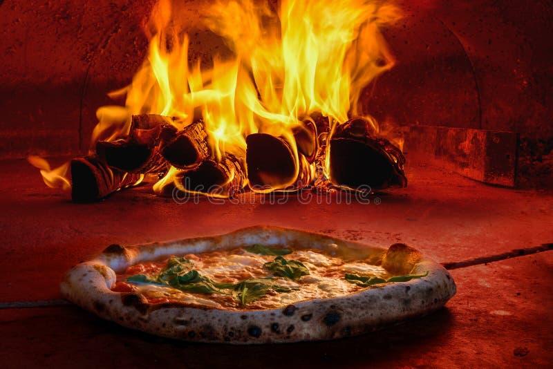 La pizza en bois a mis le feu au four avec le feu ouvert photo libre de droits