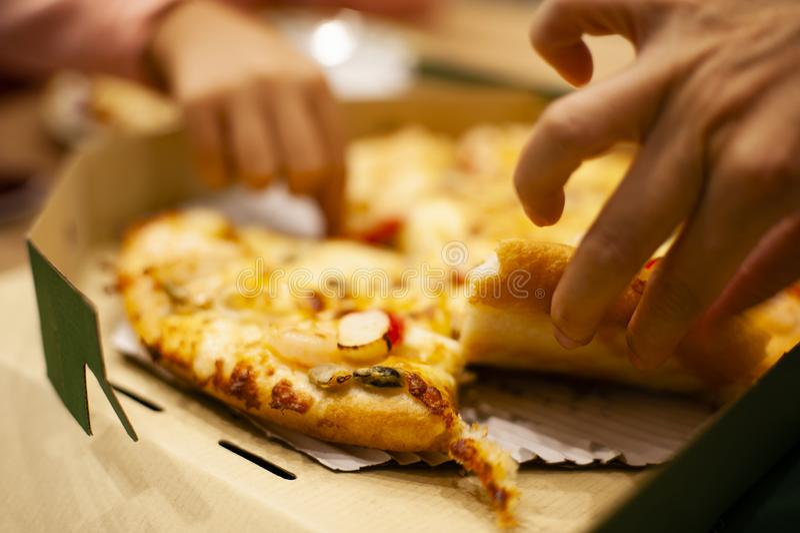 La pizza en caja en la tabla en la tienda de la pizza era selección a comer por dos manos de hija y de madre para la cena foto de archivo