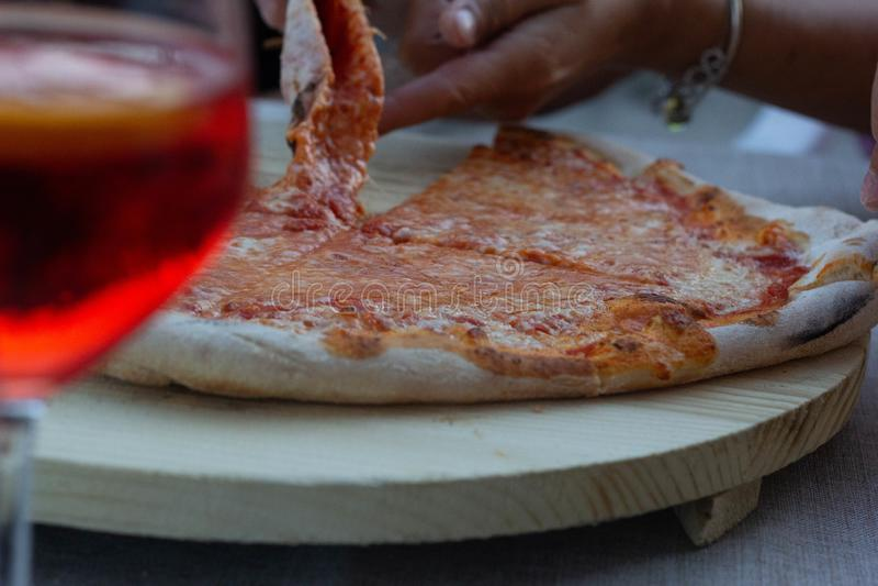 La pizza es un producto gastronómico sabroso que se compone de una pasta hecha de la harina, del agua y de la levadura se aplana  fotografía de archivo