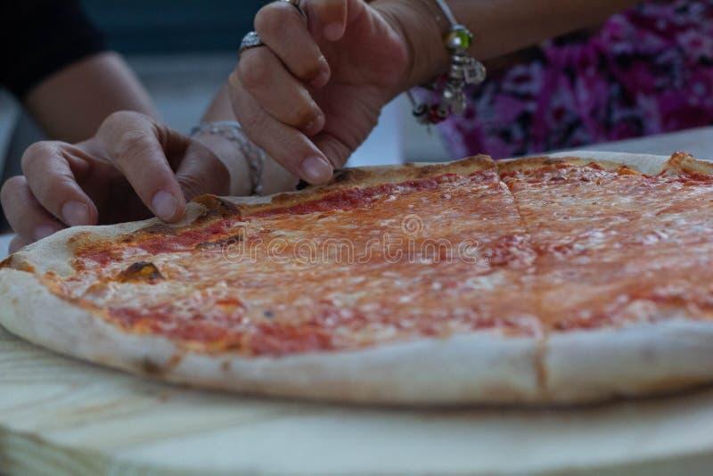 La pizza es un producto gastronómico sabroso que se compone de una pasta hecha de la harina, del agua y de la levadura se aplana  fotografía de archivo libre de regalías