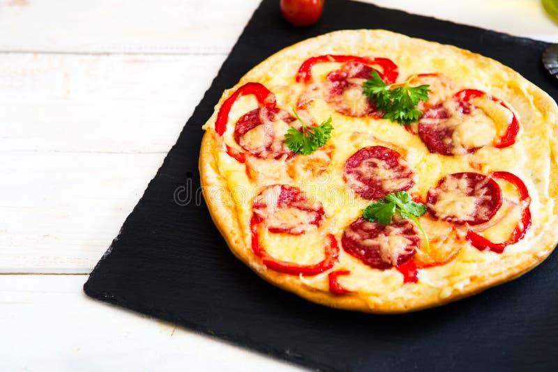 La pizza fresca deliciosa sirvió en la tabla de madera blanca y la superficie de piedra negra Copie la composición del espacio fotos de archivo