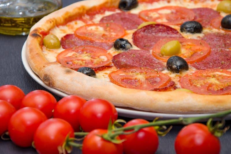La pizza italiana con la salchicha y las aceitunas está en la tabla cerca de la ventana, la comida en la pizzería fotografía de archivo libre de regalías