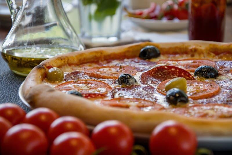 La pizza italiana con la salchicha y las aceitunas está en la tabla cerca de la ventana, la comida en la pizzería imágenes de archivo libres de regalías