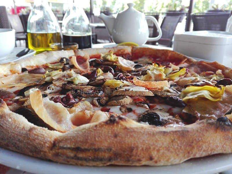 La pizza prête sur la table est coupée et mangée photographie stock libre de droits