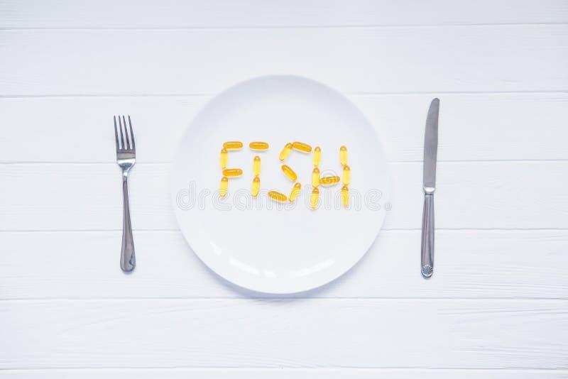 La placa blanca de la visión superior con los pescados redacta las letras por las cápsulas del aceite de hígado de bacalao, Omega imagen de archivo