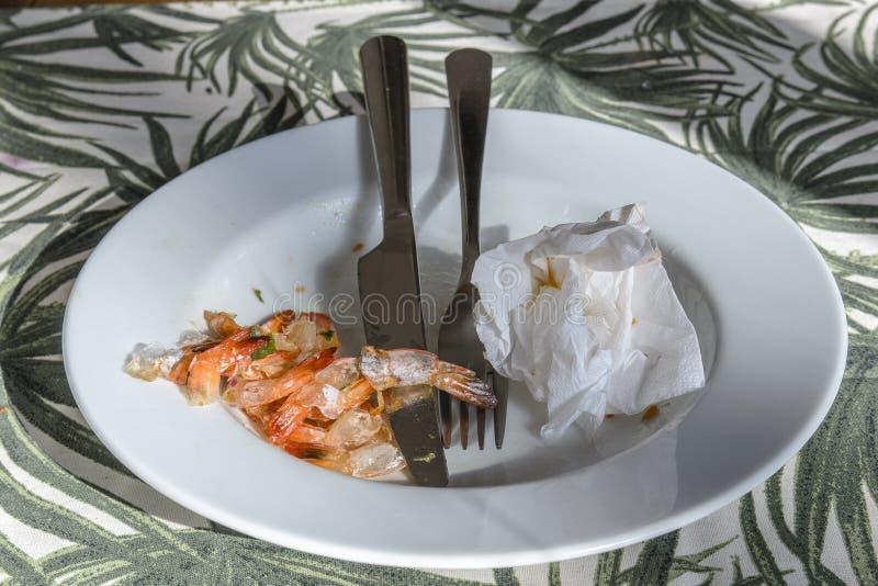 La placa con una bifurcación y un cuchillo se coloca con sobras y sobras cena deliciosa con los mariscos de las gambas del rey foto de archivo libre de regalías