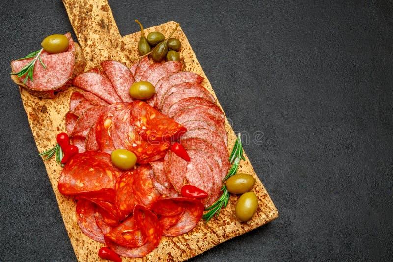La placa de la carne fría con la salchicha del salami y del chorizo en la madera del corcho sube foto de archivo libre de regalías