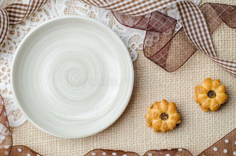 La placa de cerámica vacía con la galleta del coco y la piña atascan foto de archivo libre de regalías