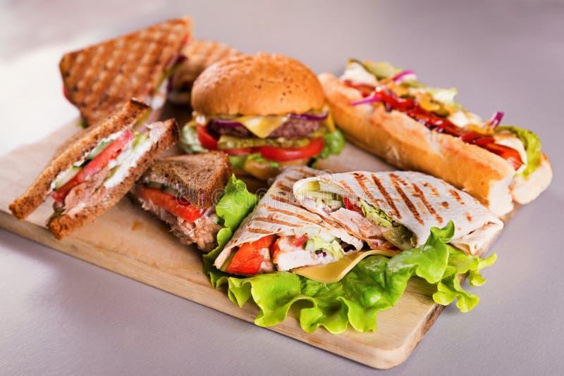 La placa de los alimentos de preparación rápida con el perrito caliente de la hamburguesa intercala el abrigo del pollo fotografía de archivo libre de regalías