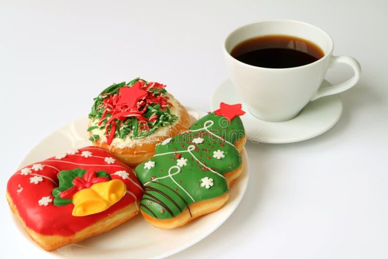 La placa de la Navidad adornó los dulces en una placa blanca servida en la tabla blanca con una taza de café foto de archivo