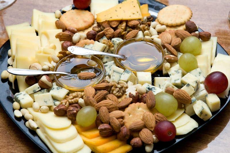 La placa de queso sirvió con las nueces, las uvas, la miel y las galletas imagen de archivo libre de regalías