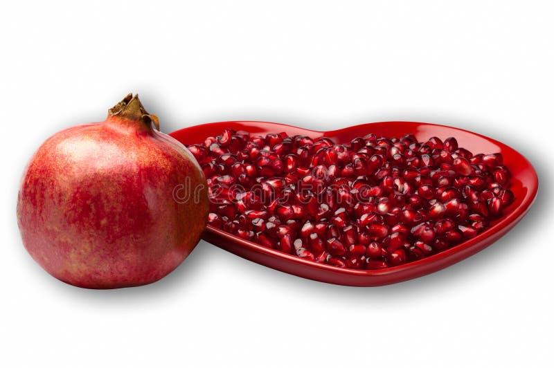 La placa en forma de corazón roja de la granada jugosa madura deliciosa siembra por completo la fruta entera y el fondo blanco fotos de archivo libres de regalías